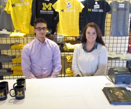 Male and female student at registration table in lobby selling shirts, mugs and books