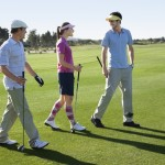 Three golfers talk as they walk out onto the course