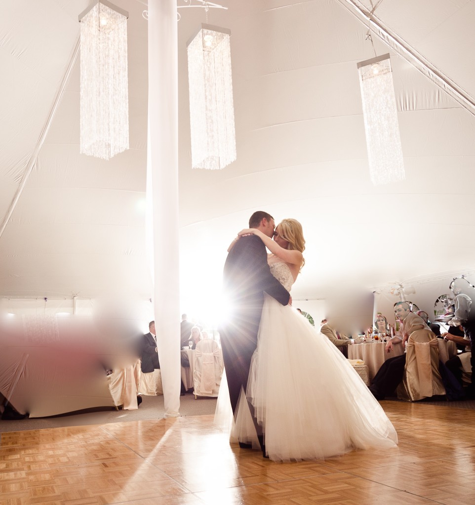 The Sun Glares In Enviously On A Bride And Groom Dancing Close Hall