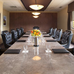The long marble conference room table, each seat comes equipped with a folder and a wine glass