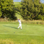 A golfer takes a swing with his club from the center of a clearing on the golf course