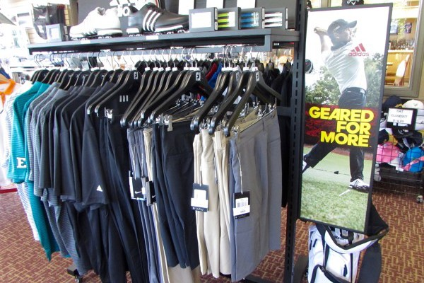 Shirts hang side by side on a rack in the golf shop