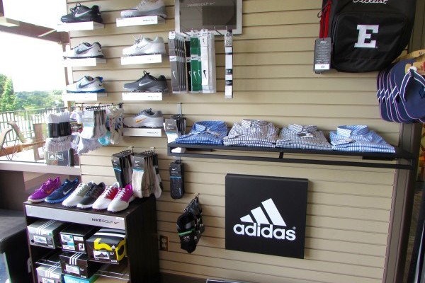 Golf shop with bags, shoes and shirts on display racks on the wall