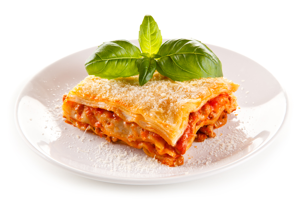 Photo of lasagna on white plate with garnish on top